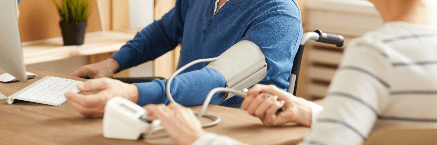 White male having his blood pressure taken with an arm fastening. You can only see the man's arm and a white woman pressing the blood pressure machine.