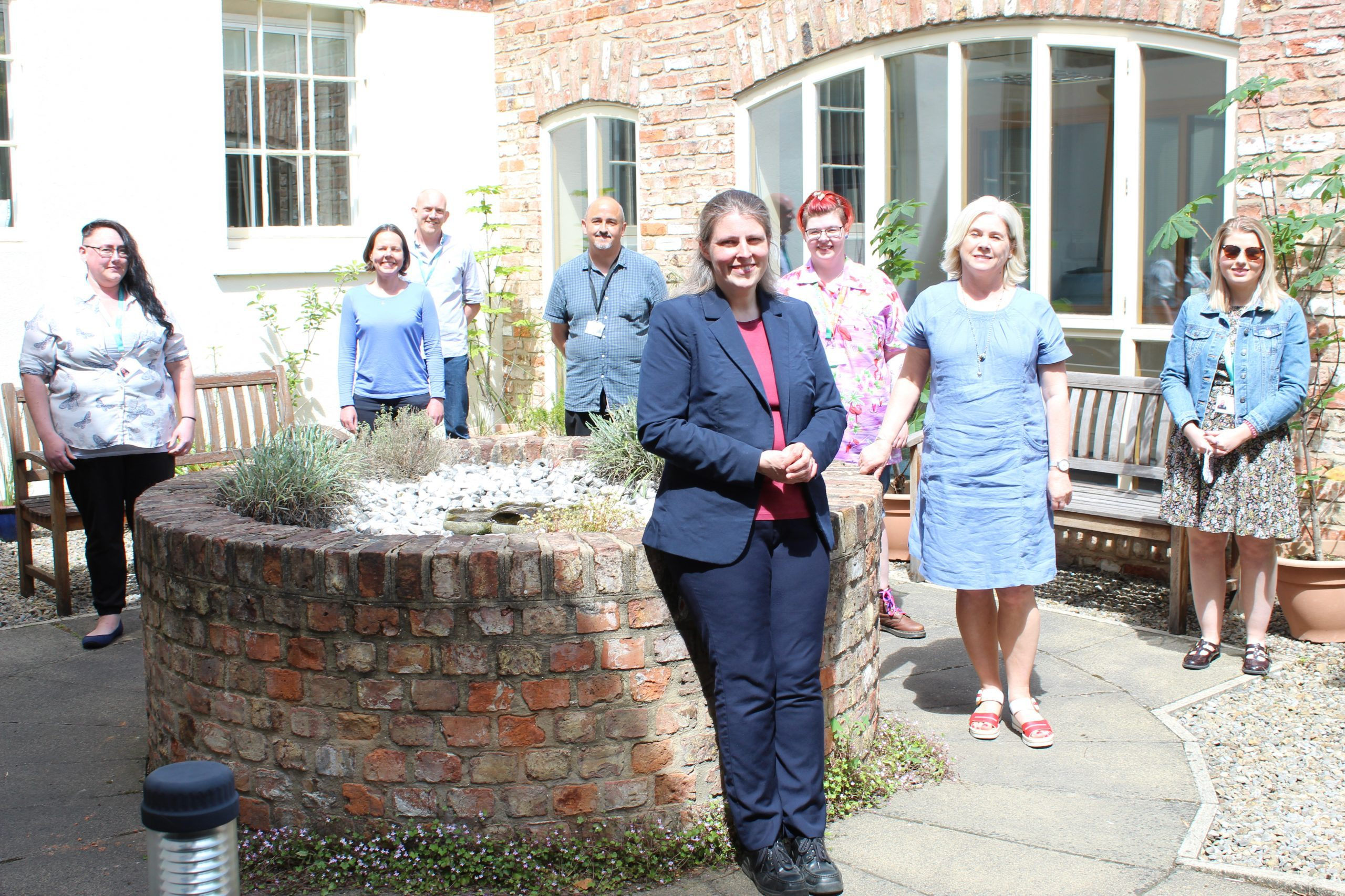 8 people, 6 female and 2 male, stood spaced apart in a courtyard area. There is a raised brick cirucular fountain in the middle and brick wall with large windows behind them. Everyone is smiling and looking at the camera.