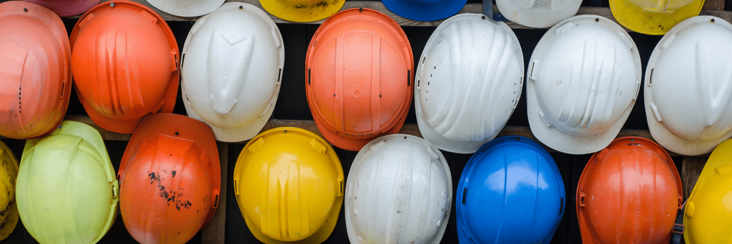 Lots of different coloured hard hats all hung on a wall