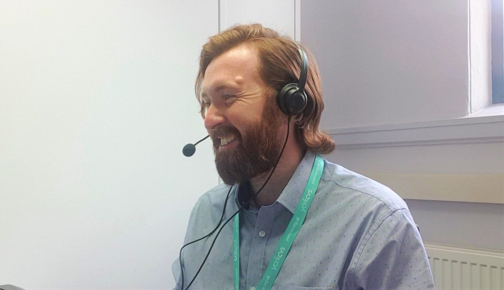 A photo of Drew Richardson (Volunteer Centre Manager at York CVS), a white man with medium length red hair and beard, in a blue shirt, wearing a York CVS lanyard, talks to someone over a computer headset.