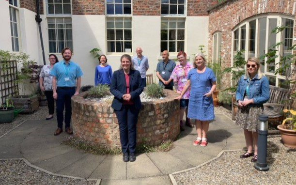 A photo of Rachael Maskell (local MP and Shadow Minister for the Voluntary Sector and Charities) and different representatives from the local VCSE Sector stood in the courtyard of the Priory Street Centre.